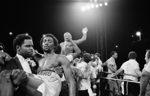 "Thomas ""Hitman"" Hearns is carried from the ring in Las Vegas Monday night, April 15, 1985 as Marvelous Marvin Hagler celebrates his undisputed world middleweight championship.   Hagler knocked out Hearns in the third round of the fight. (AP Photo)"